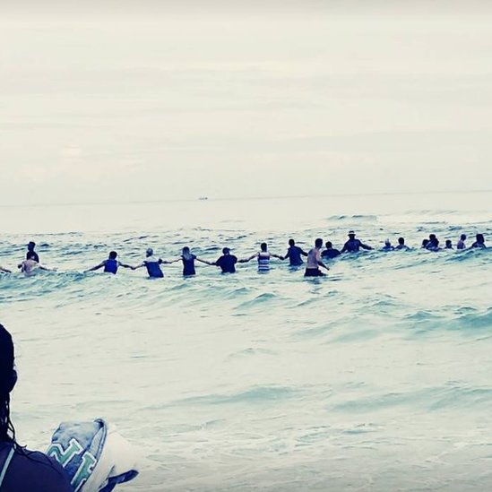 Image of people holding hands in the water to save drowning family