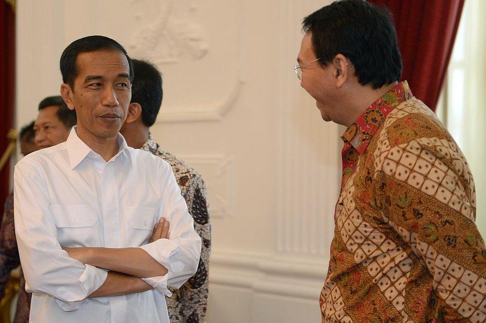 Indonesian President Joko Widodo (L) listens to acting Jakarta Governor Basuki Tjahaja Purnama alias Ahok (R) at the presidential palace in Jakarta on October 22, 2014.