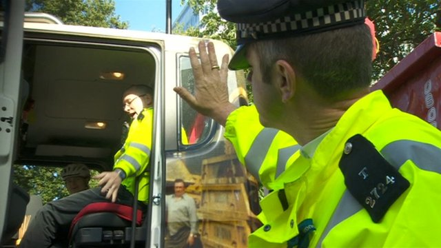 A police officer waves to cyclist Philippa Gregory who's sat in the driver's cab