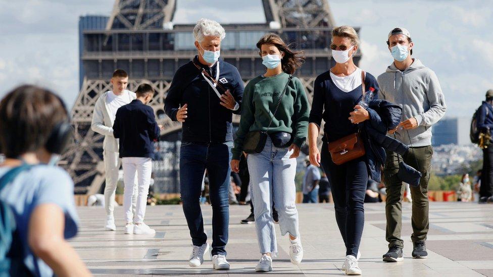 People wear facemasks near the Eiffel Tower