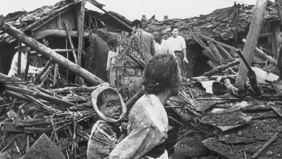 An elderly woman and her grandchild wander at their wrecked home in the aftermath of an air raid over Pyongyang, circa 1950