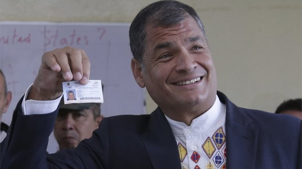 Ecuador's President Rafael Correa holds up his voter ID after casting his ballots in general elections in Quito, Ecuador, Sunday, Feb. 19, 2017.