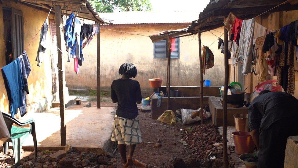 Una mujer joven en el patio de su casa n Guinea.