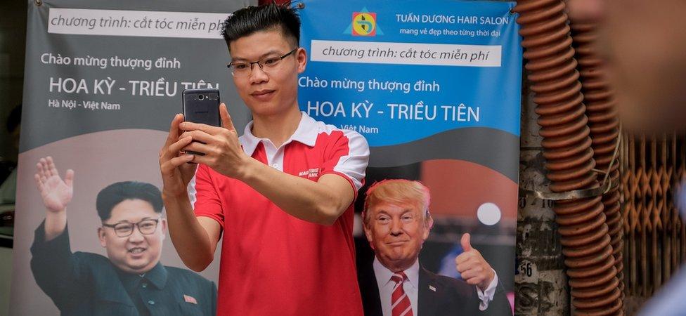 Momak stoji ispred postera za samit u Hanoju, 20. februara 2018. godine