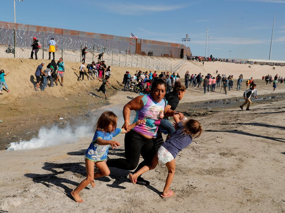 A woman runs away from tear gas with her two children