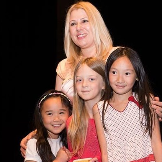 Susan Polgar poses for a picture hugging young girl chess players