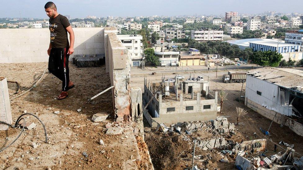 Un hombre parado entre los escombros en Gaza