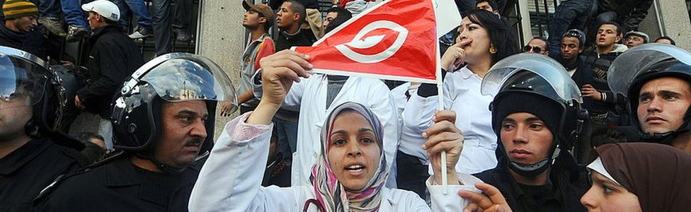 Tunisian demonstrator, holding her national country flag, is surrounded by police as she rallies in 2011