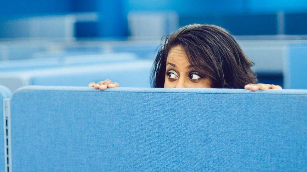 Mujer espiando en el lugar de trabajo.
