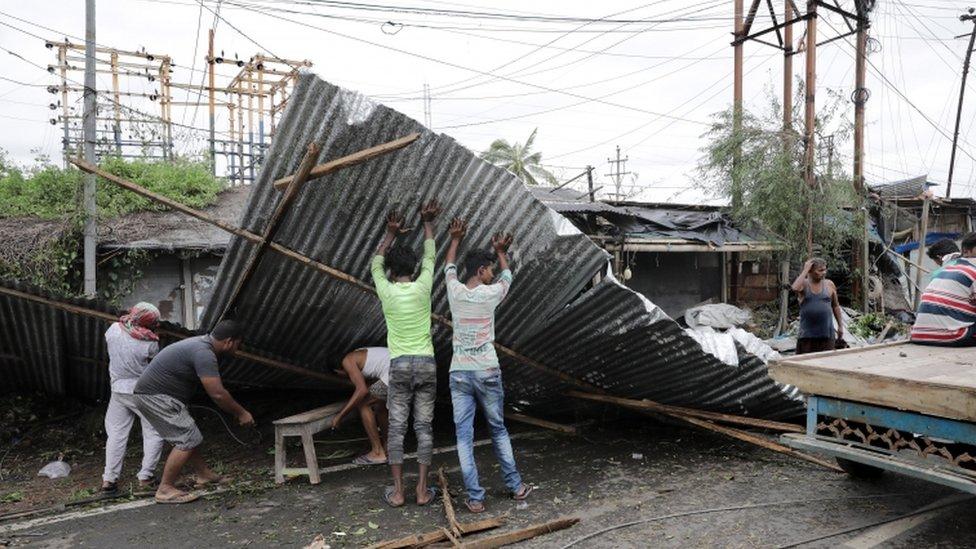 Hombres levantan chapas volcadas por el ciclón en Bokkhali, India.