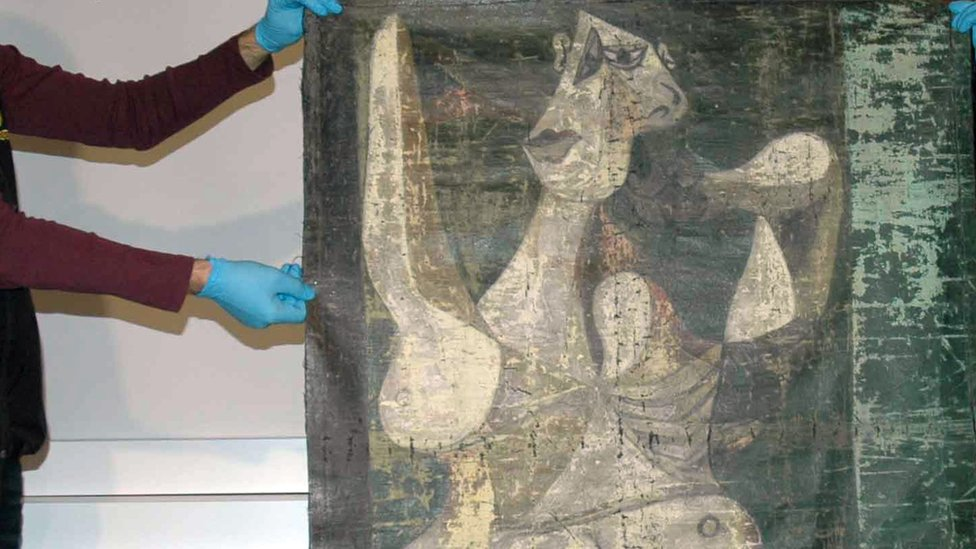 Police officers hold what is thought to be a Picasso painting in Istanbul, 30 January 2016.