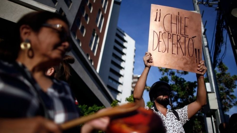 """A demonstrator bangs a pot as another holds a sign reading """"Chile has woken up"""" as they demonstrate in Santiago on 21 October, 2019."""