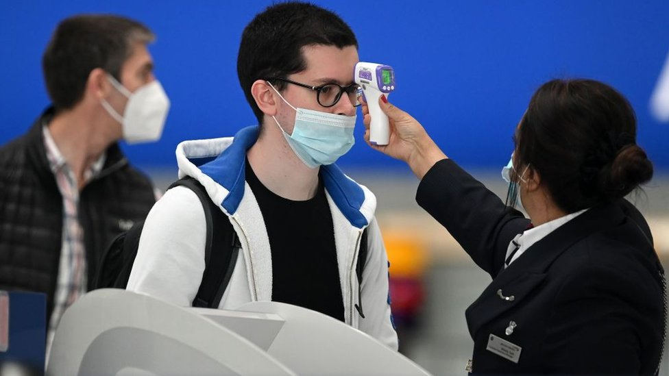 Passengers have their temperature checked when checking in for flights at Heathrow Airport
