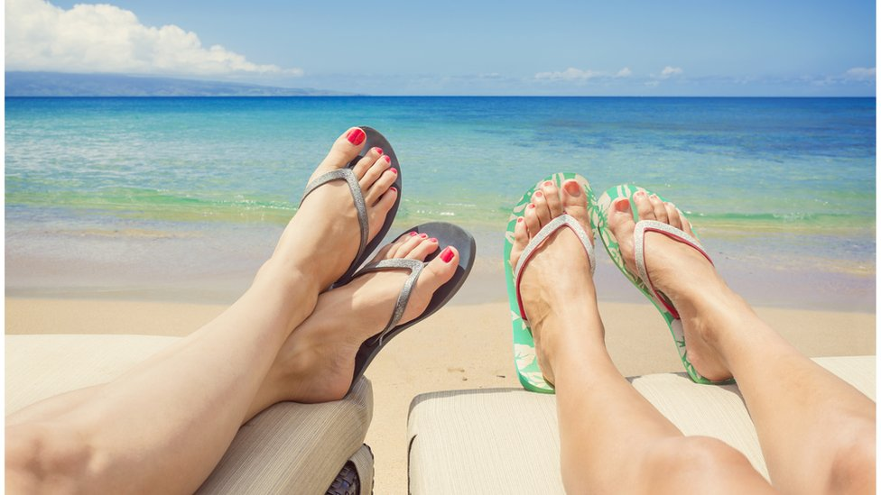 Two women lie next to one another on sun loungers wearing flip flops with the ocean in the background