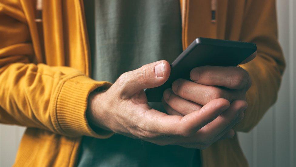 manos agarrando teléfono