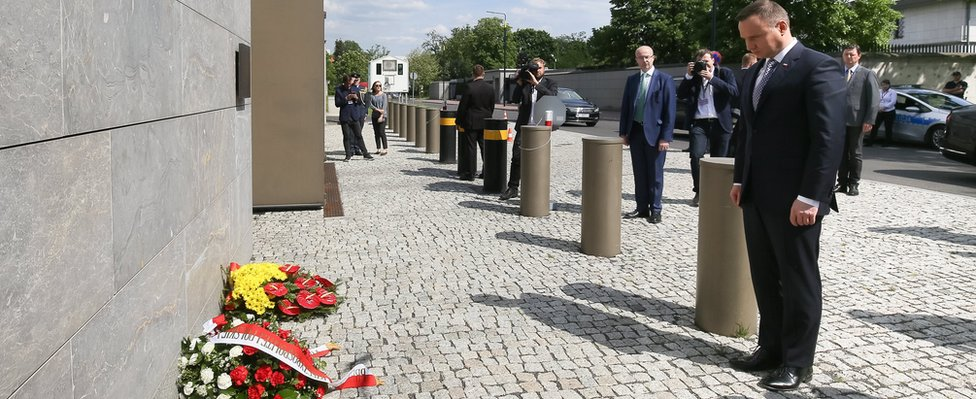 Polish President Andrzej Duda (R) bows after placing flowers in front of the British Embassy in Warsaw (23 May)