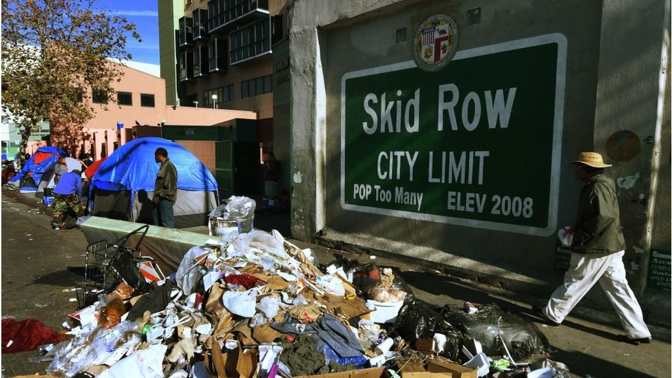 Trash and tents in front of a mural reading 'Skid Row, population too many, elevation 2008'