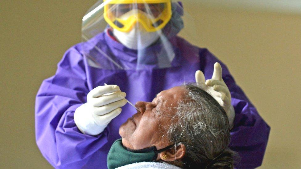 Un sanitario toma una muestra nasal de un paciente.