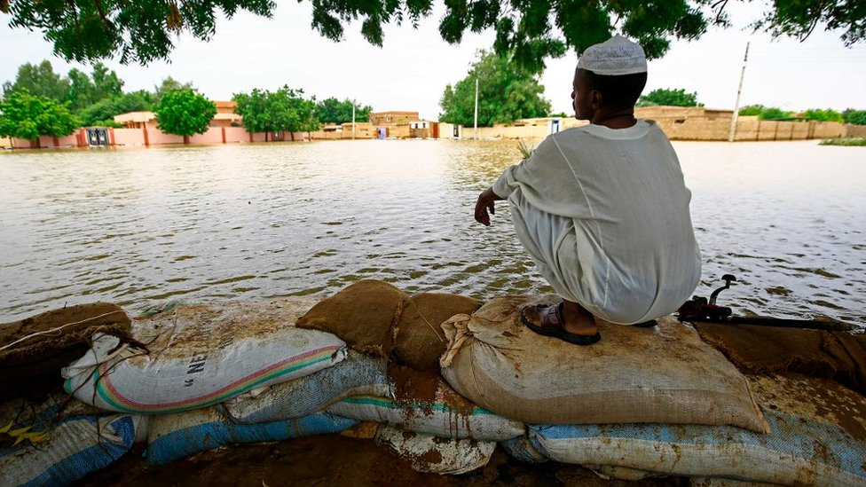A Sudanese resident sits on flood barriers in the capital Khartoum's southern neighbourhood of al-Kalakla, on August 31, 2020.