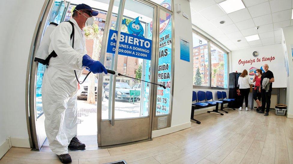 İspanya'da bir çamaşır yıkama dükkanı dezenfekte ediliyor