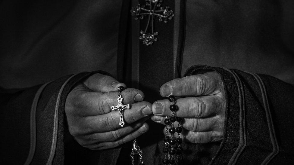 Manos de cura con un rosario