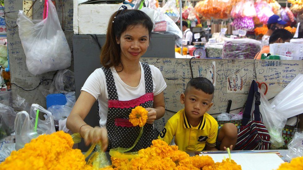 A young Thai woman and a child in a market
