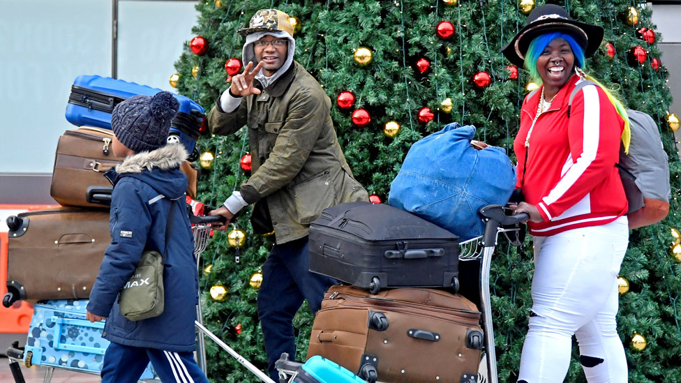 A family with suitcases at Gatwick