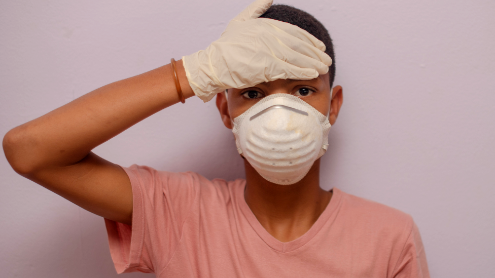 A boy in South Africa wearing a face mask and gloves