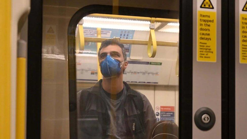 Homem de máscara viaja de pé no metro