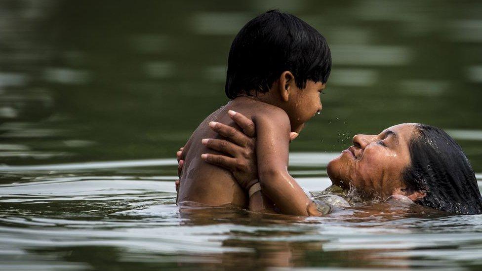 Mulher nada com criança pequena em rio em Palmas, no Tocantins