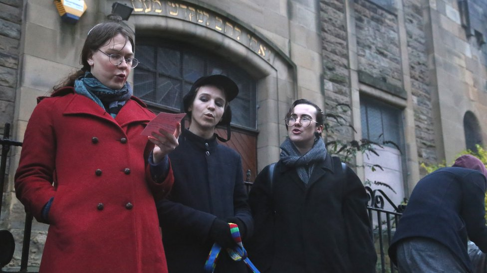 Three Jewish people singing outside the synagogue