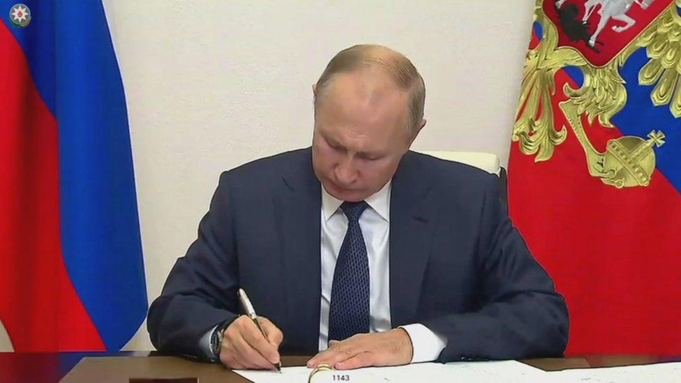 El presidente ruso Vladimir Putin firma documentos en la residencia estatal Novo-Ogaryovo en las afueras de Moscú, Rusia