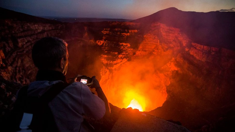 Un turista le toma una foto a la caldera hirviente del volcán Masaya