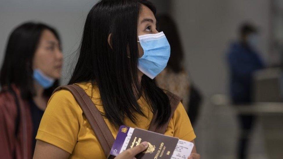 Mujer con barbijo y pasaporte