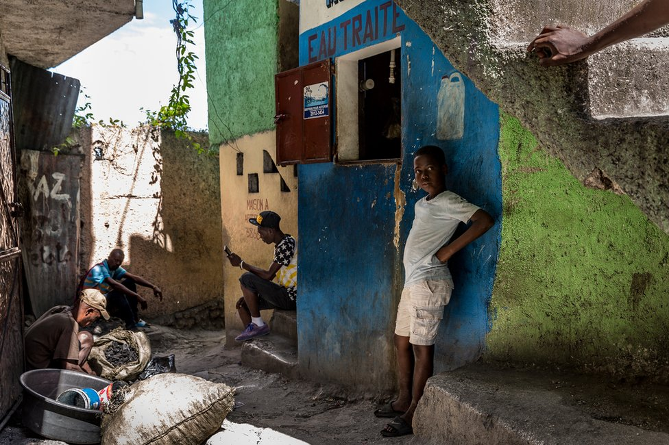 A boy stands and looks at one of the crossroads within the slum. A man on the left is tending to his charcoal shop