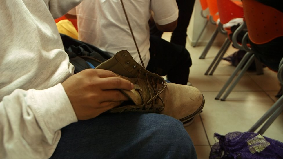 A man threads laces in to his shoes