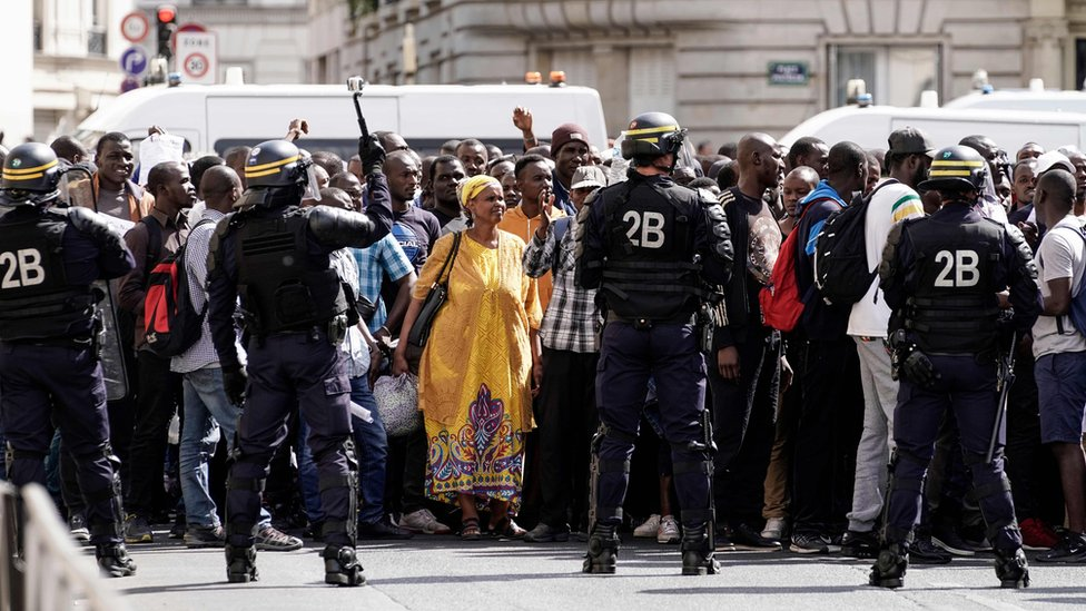 French police officers stand as undocumented migrants demonstrate at the Panthéon