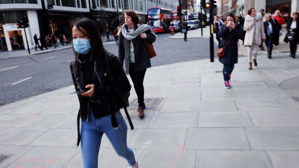 Personas en la calle, algunas con mascarillas, durante el brote de coronavirus en Londres, antes de la orden de confinamiento