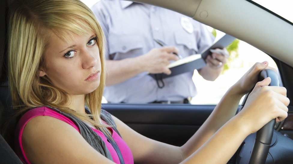 Annoyed young woman being given a speeding ticket by a policeman