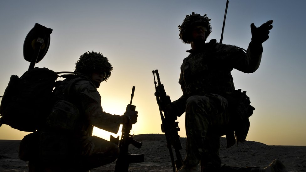 British soldiers pictured in silhouette during a dawn patrol in the Nahr-e Saraj district of Helmand Province, Afghanistan