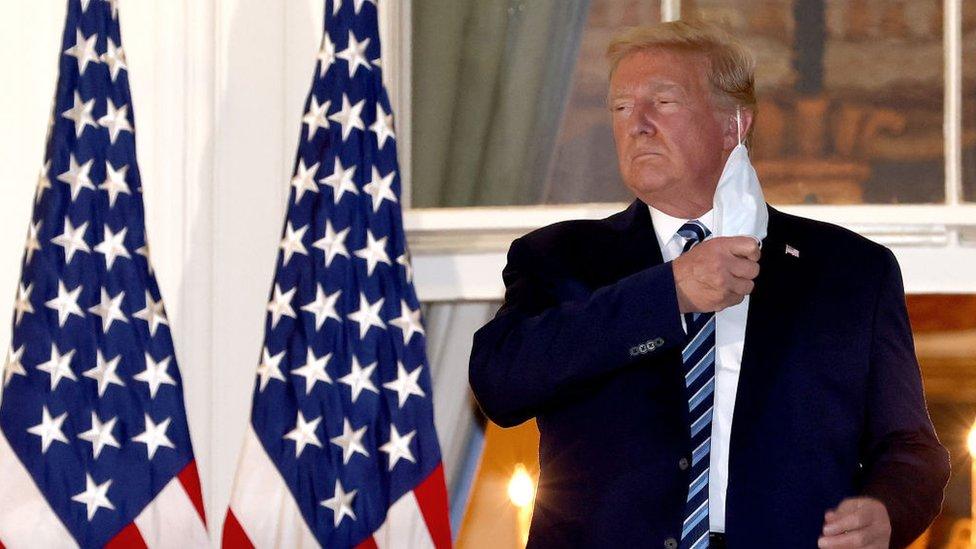 Presiden AS Donald Trump melepas topengnya saat kembali ke Gedung Putih dari Pusat Medis Militer Nasional Walter Reed pada 05 Oktober 2020 di Washington, DC