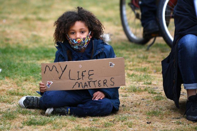 """Un niño protesta con una pancarta que dice """"Mi vida importa""""."""