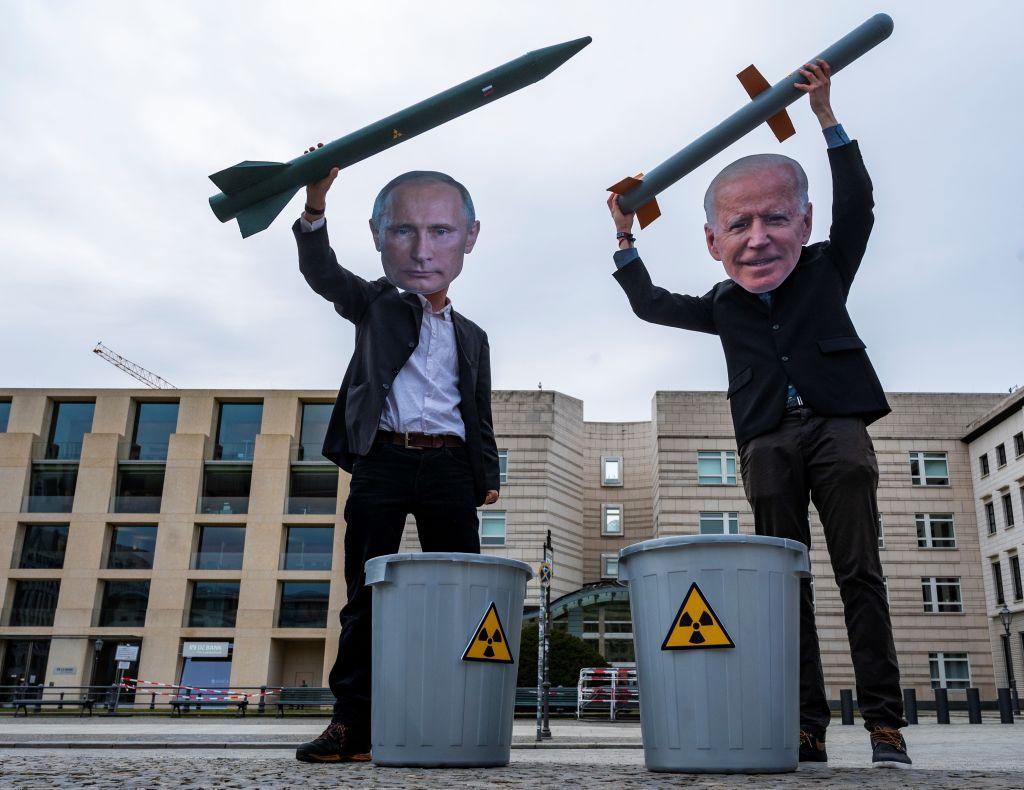hombres con mascaras de Putin y Biden