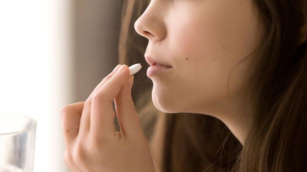 Una mujer tomándose una pastilla