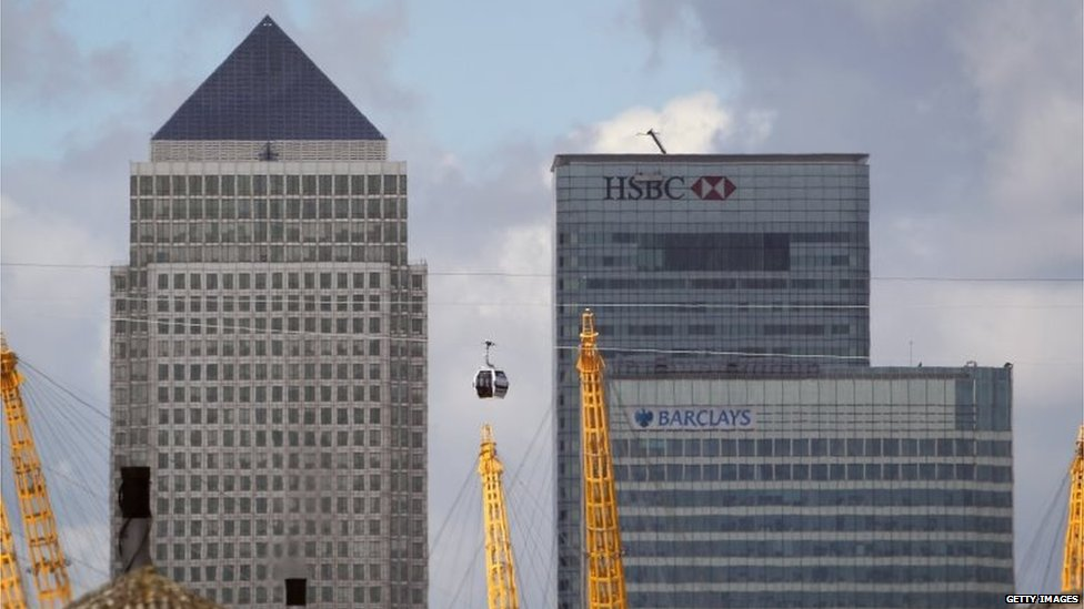 Transport for London (TfL) Emirates Air Line cable car passes over the River Thames in front of the Canary Wharf business district