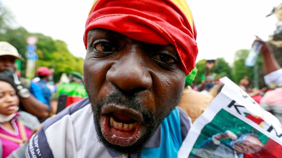 A man with the Cameroonian flag wrapped around his head looks down the camera lens.