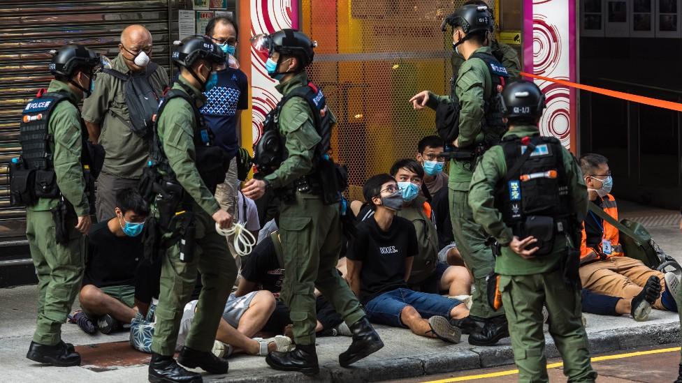 Manifestantes jóvenes detenidos sentados en el piso rodeados por policías en Hong Kong