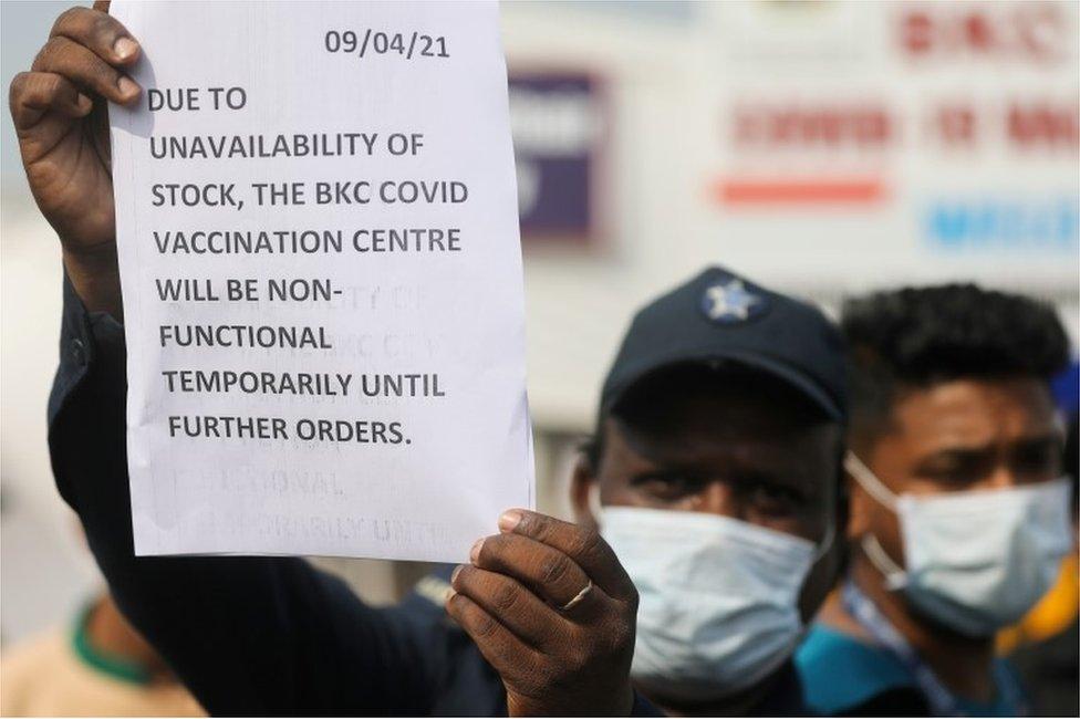 Um guarda segura um aviso para informar às pessoas sobre a escassez de suprimentos de vacina contra o coronavírus em um centro de vacinação em Mumbai, Índia, em 9 de abril de 2021