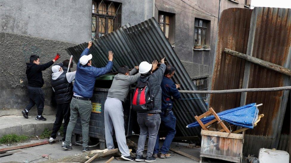 Un grupo de personas coloca barricadas para cerrar los accesos a la céntrica plaza Murillo, en torno a la cual tienen su sede los poderes del estado en La Paz.