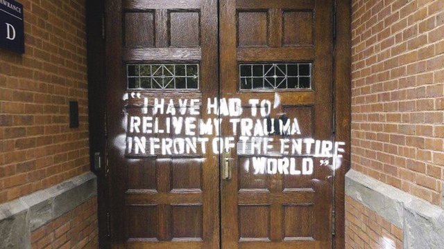 "Photo of graffiti on a door that reads ""I have had to relive my trauma in front of the entire world"""